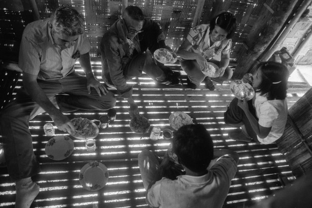 Missionary Boe Stanley (left) enjoys a meal with some friends as sunlight shines through a split-bamboo floor in the rural Philippines. Rutledge was a master of capturing light and darkness in his photographs.