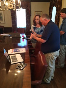 TAB executive editor Jennifer Rash shows SBOM's Brian Harris and Doug Rogers how augmented reality works during a Periscope broadcast earlier today.